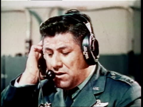 Tense military officers on telephones in control room during Cold War / flashing red light during emergency / man in military uniform talking into...