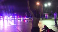 Tensions flared in the US city of Ferguson late Sunday as looters targeted at least one store following a day of somber remembrance to mark the...
