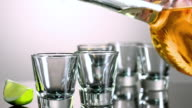 MS Tequila being poured into short shot glasses/ Los Angeles, California, United States