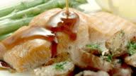 CU  teriyaki sauce poured over salmon steak served on dinner plate with asparagus and potatoes