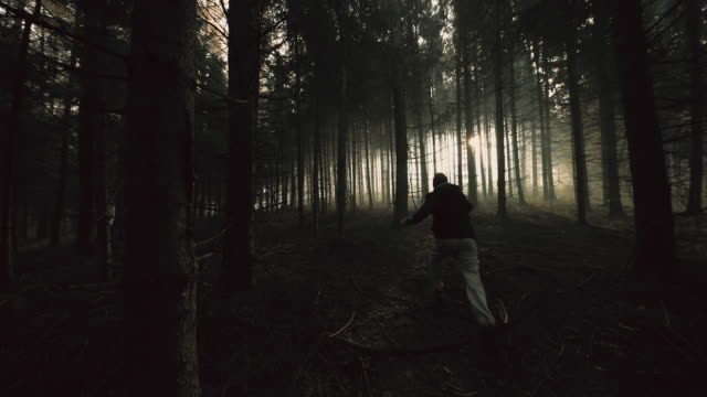 Terrified young man running in a dark forest