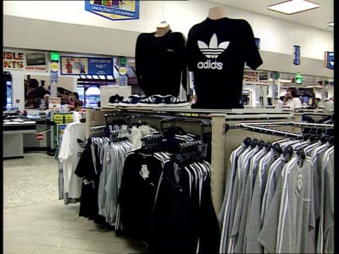 Tesco /Adidas deal ITN Adidas shoes being put on shelves in Tesco store Adidas clothing on display Christine Cross intvwd Talks of reasons for...