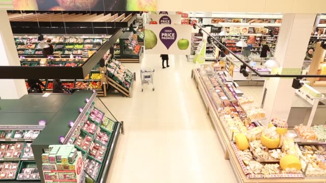 Tesco Price Promise promotional signage inside a Tesco Plc supermarket in Kensington west London High angle view shoppers walking through supermarket...