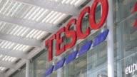 Tesco signage on exterior of supermarket building at a Tesco Plc supermarket in Kensington West London Tesco sign on building wall Wide shot Tesco...