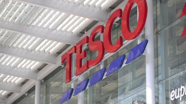 Tesco signage on exterior of supermarket building at a Tesco Plc supermarket in Kensington West London Tesco sign on building wall Wide shot Tesco...