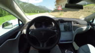 FPV: Tesla electric car Self driving and turning on local road. Autonomous vehicle driving without a driver