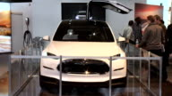 WS Tesla sign TILT DOWN to Model X front end as falconwing door is closing / WS rear end ZI to CU of vanity plate / MS passenger side rear door woman...