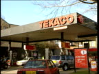 Texaco petrol station general views ENGLAND London EXT/ITN GVS man filling car on forecourt of Texaco petrol station / GV forecourt ZOOM to word...