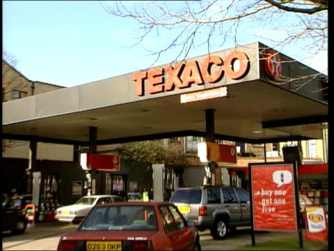 Texaco petrol station general views ENGLAND London EXT/ITN GVS man filling car on forecourt of Texaco petrol station / GV forecourt ZOOM to word...