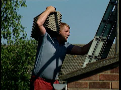 Derek Elsom house owner surveying damage to roof TILT UP as roofer up ladder to roof carrying roofing tiles Roof stripped roofer carrying up tiles to...