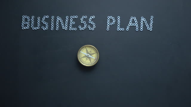 Text BUSINESS PLAN written With Screw Nuts On Blackboard And Compass