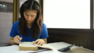 Thai girl student highlight note on old book