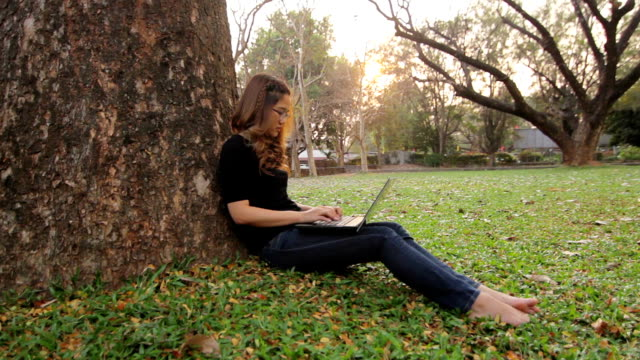 Thai girl using laptop at outdoor park