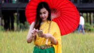 Thai woman dressing with traditional style using mobile phone