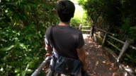 Thai young man walks down on  highly slope ladder in tropical forest