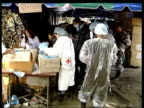 British Victims THAILAND Phuket Dead bodies covering the ground outside mortuary GV Coffins piled up in rows as soldiers carry another past LR TMS...