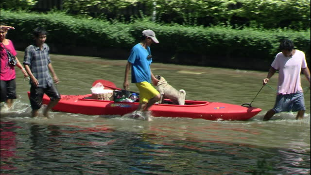 A Thailander wades through a flooded street pulling a kayak loaded with a dog and personal possessions