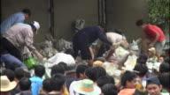 Thailanders frantically pass sandbags in a human chain as floods threaten