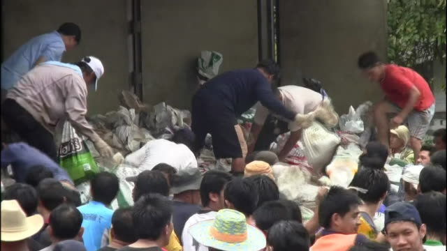 Thailanders frantically pass sandbags in a human chain as floods threaten