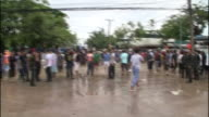Thailanders gather in an open area as muddy flood water begins to rise