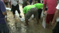 Thailanders line up sandbags on a flooded road