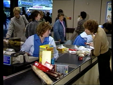 Thatcher 10th anniversary R 211184 MS Cashier working till at supermarket checkout as assistant puts food in plastic bag and shopper writes cheque...