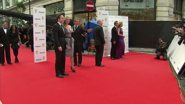 The 2010 BAFTAs held at the Royal Opera House London Shows exterior shots of Rafe Spall and Elize Du Toit posing for photographers on the red carpet