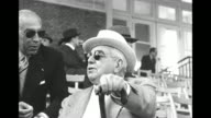 The Aga Khan speaks to man as they attend the Grand Prix de Deauville in 1950 he is seated wears sunglasses holds a cane