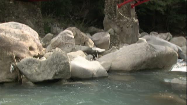 The Aizu River flows around boulders under a red bridge at the Kizetsukyo Gorge.