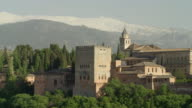 LS PAN The Alhambra of Granada with the Sierra Nevada mountain range in background; pan starts approximately at the Torre de Comares, then passes the palace of Charles V, ending at the Alcazaba