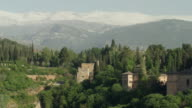 LS PAN The Alhambra of Granada with the Sierra Nevada mountain range in background; pan starts  at the Generalife and covers the entire complex, ending at the Alcazaba
