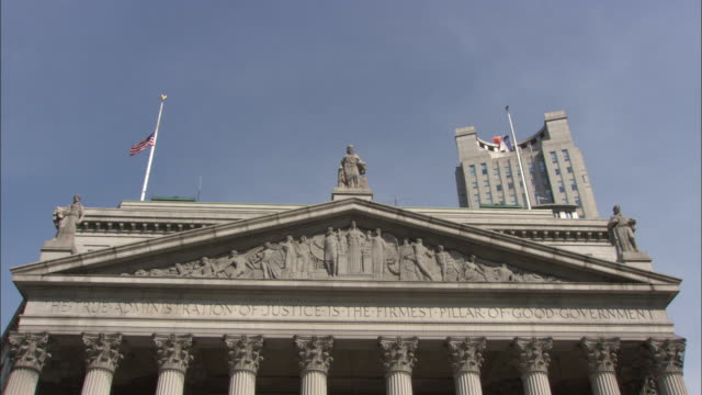 The American flag flutters at half-mast on top of the New York Supreme Court building.