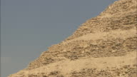 The ancient Saqqara Pyramid contrasts against a pale blue sky.