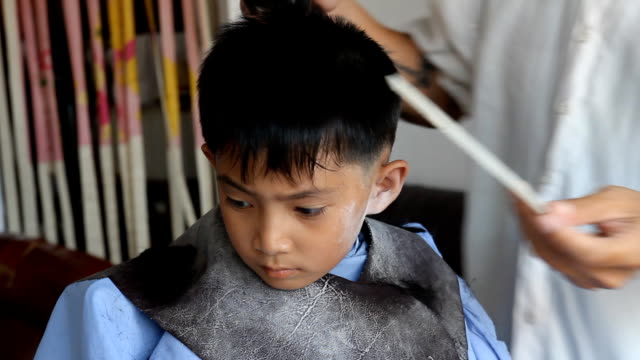 The Asian boy having a haircut.