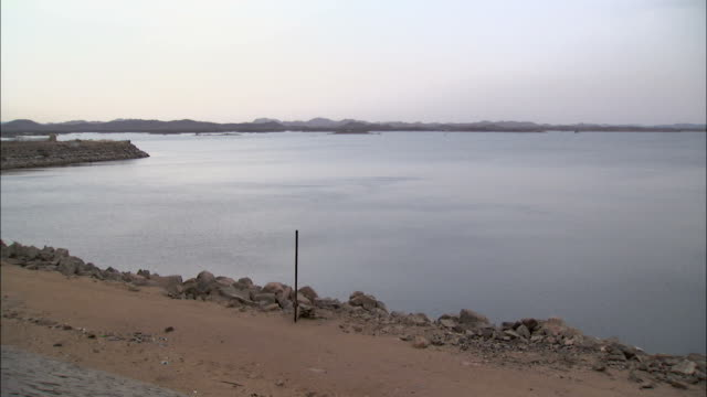 The Aswan High Dam lines a shore of the Aswan High Dam Reservoir.\n Available in HD.