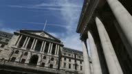 The Bank of England headquarters stands on Threadneedle Street as pedestrians walk past and people sit on the steps of the Royal Exchange on a sunny...