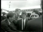 The Beatles walking down steps of their plane including Jimmy Nicol / Fans waving to band from balcony outside airport / The Beatles along tarmac...