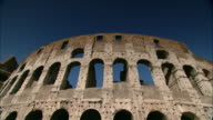 The blue sky glows through the arches of Rome's ancient Colosseum.