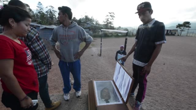 The body of Edgard Ramirez is moved to a football pitch after five people were fatally gunned down in his family home in Honduras late Monday as they...