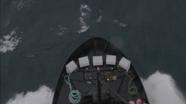The bow of a fishing vessel cuts through a sea.