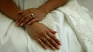 The bride in a white dress sitting on the bed and turns on her finger a wedding ring