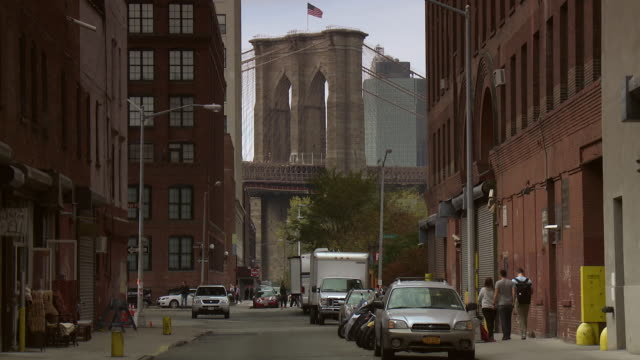 The Brooklyn Bridge sits down at the end of an old street in the DUMBO area of Brooklyn.
