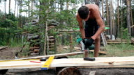 The builder cuts the wooden plank with a circular saw.