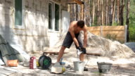 The builder mixes cement and water in a bucket.