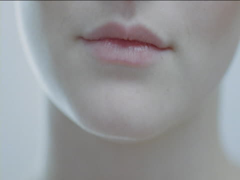 The camera pans across to a close-up of the bottom half of a woman's face. She smiles, revealing perfect teeth, then bites her bottom lip as though trying not to laugh.