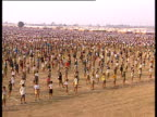 The camera pans over a large group of people standing in rows in a field