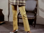 The camera pans up a model wearing a trouser suit and hat designed by Mattli 1970