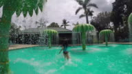 The camera runs after little girl at waterpark, through the water drops falling off the plastic palm trees.