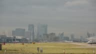 The Canary Wharf business and shopping district stands on the skyline as a small passenger aircraft takes off from the runway of London City Airport...