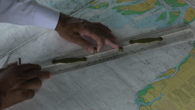 The captain of the Greenpeace Rainbow uses maps and charts to plot his next course whilst berthed at Chittagong in Bangladesh during its conversion to a hospital ship